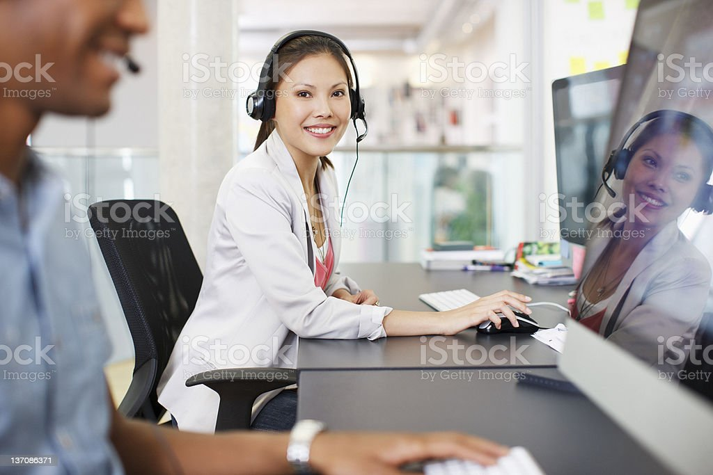 Portrait of confident businesswoman with headset at computer in office royalty-free stock photo