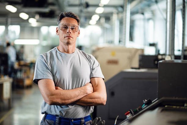 Portrait of confident CNC machine operator in a factory. Portrait of industrial engineer with arms crossed standing by CNC machine and looking at camera. metal worker stock pictures, royalty-free photos & images