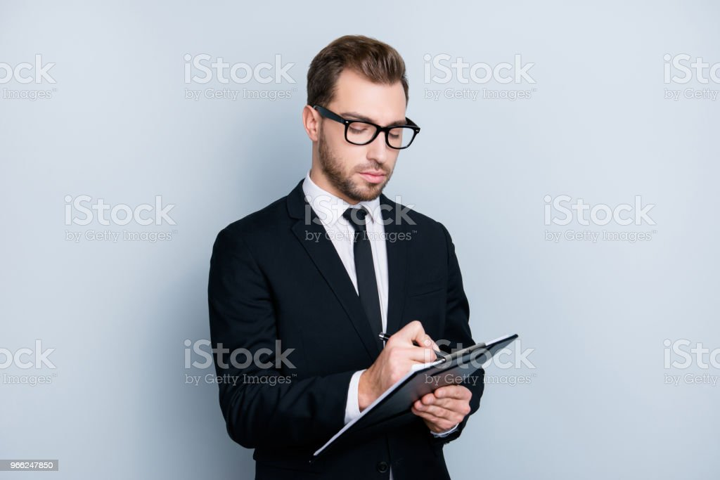Portrait of confident concentrated self-assure handsome bearded smart clever guy writing information to the documents on clipboard in hid hands, isolated on gray background, copy-space stock photo