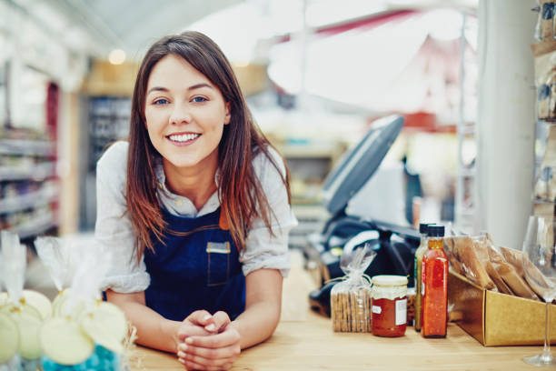 portrait of confident deli owner leaning on checkout counter - store counter stock photos and pictures