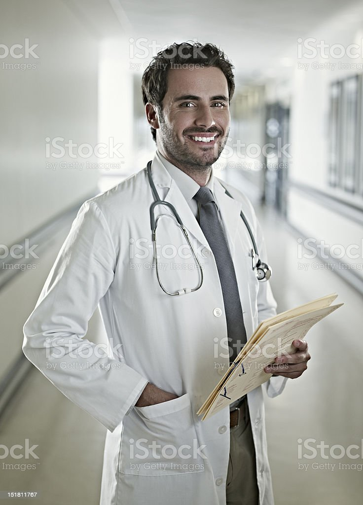 Portrait of confident doctor holding medical record in hospital corridor stock photo