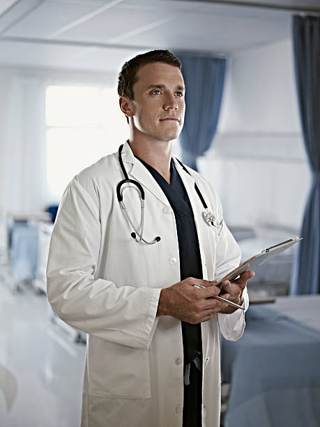 Portrait of confident doctor holding medical record in hospital room stock photo