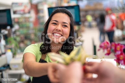 istock Portrait of confident employee checkout giving a flower at flower market 1037572334