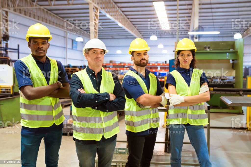 Portrait of confident engineers in industry Portrait of confident engineers standing in factory. Colleagues are with arms crossed working in manufacturing company. Production workers are wearing reflective clothing and hardhats. 20-24 Years Stock Photo