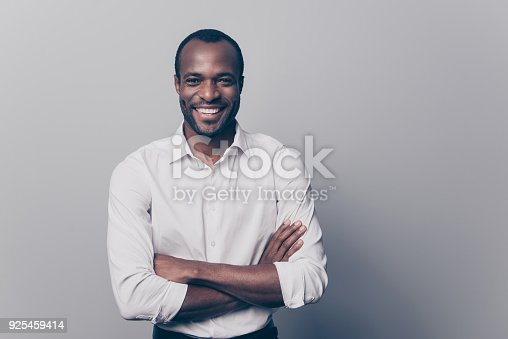 istock Portrait of confident experienced qualified smart intelligent clever laughing afro man with toothy beaming smile dressed in white classic shirt with folded hands isolated on gray background 925459414