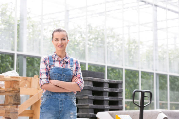 Portrait of confident farmer with pallets against greenhouse stock photo