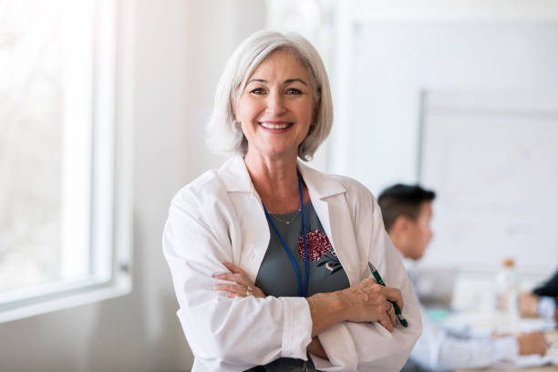 Portrait of confident female doctor Beautiful mature Caucasian female doctor smiles cheerfully at the camera. She is standing with her arms crossed. Her colleagues are meeting in the background. female doctor stock pictures, royalty-free photos & images