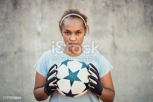 Portrait of confident female athlete holding ball. Young soccer goalkeeper is standing against wall. She is wearing sports clothing.