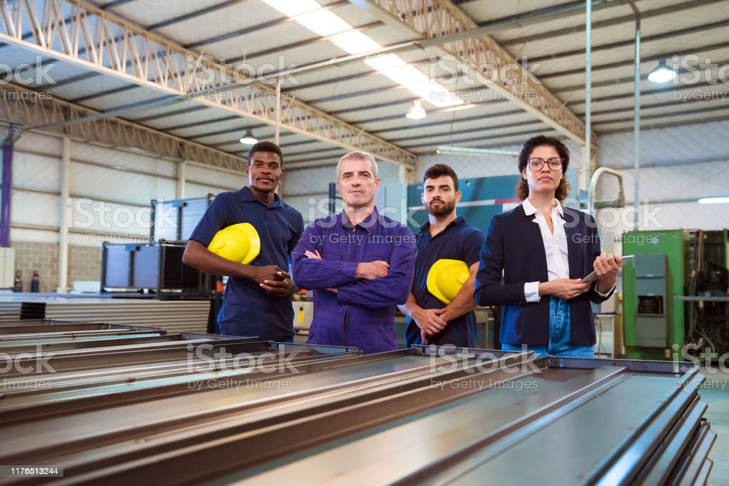 Portrait of confident female inspector and workers Portrait of confident female inspector and production workers. Expertise are related to manufacturing occupation. They are standing in factory. 20-24 Years Stock Photo