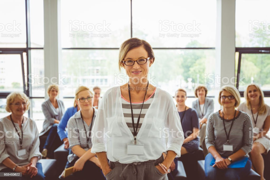Portrait of confident female presenter with audience in background Portrait of smiling presenter with female audience in background. Beautiful businesswoman looking at camera. Adult Stock Photo
