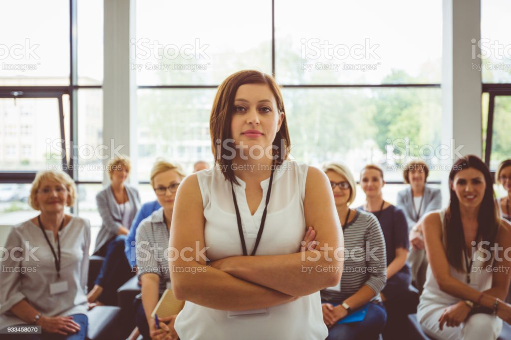 Portrait of confident female presenter with audience in background Portrait of confident presenter with female audience in background. Beautiful businesswoman looking at camera. Adult Stock Photo