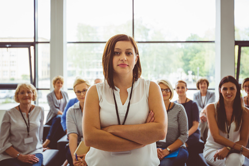 Portrait Of Confident Female Presenter With Audience In Background Stock Photo - Download Image Now