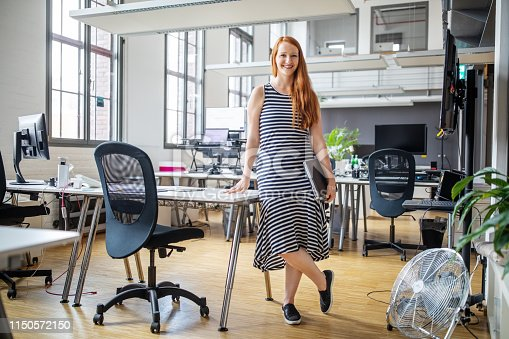 Portrait of smiling businesswoman holding laptop standing by a desk in modern office. Portrait of confident female professional in smart casuals.