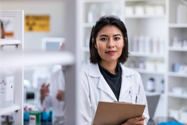 Portrait of confident female scientist Mid adult Hispanic female scientist stands in her lab. She is holding a clipboard. microbiologist stock pictures, royalty-free photos & images