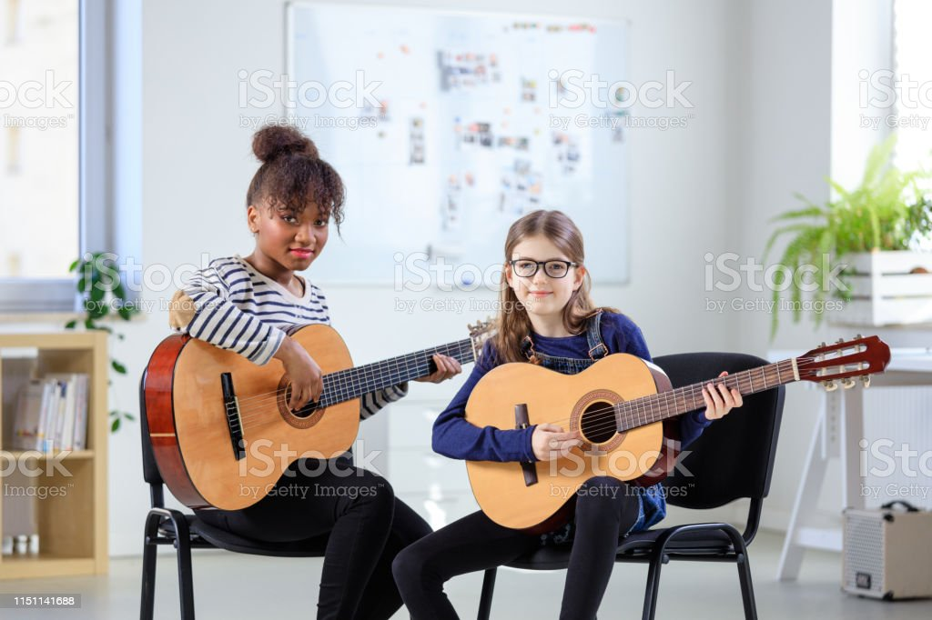 Portrait of confident guitarist and student Portrait of smiling female trainer and student in music class. Confident instructor teaching to play guitar in conservatory. They are in casuals at classroom. 10-11 Years Stock Photo