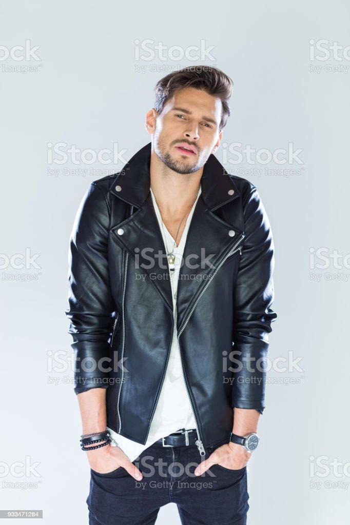 Portrait of confident, handsome man wearing leather jacket Fashion portrait of handsome man wearing black leather jacket. Studio shot, grey background. 25-29 Years Stock Photo