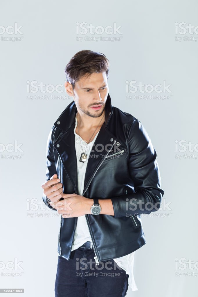 Portrait of confident, handsome man wearing leather jacket Fashion portrait of handsome man wearing black leather jacket. Studio shot, grey background. 25-29 Years Stock Photo