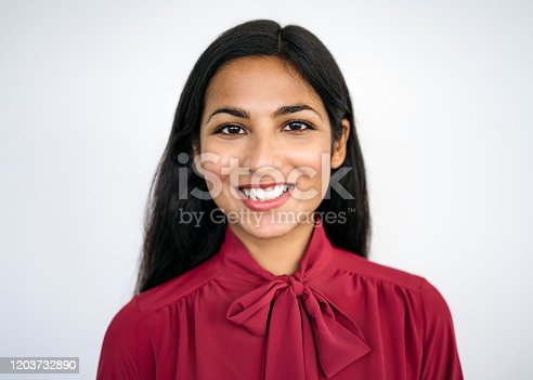 Front view close-up of young Indian businesswoman with long black hair wearing maroon blouse with tied bow and smiling at camera against white background.