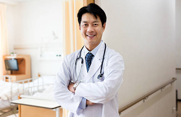 Portrait of confident japanese doctor standing outside ward stock photo