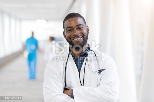 Mid adult African American male doctor stands confidently in a hospital skybridge. He is smiling at the camera.