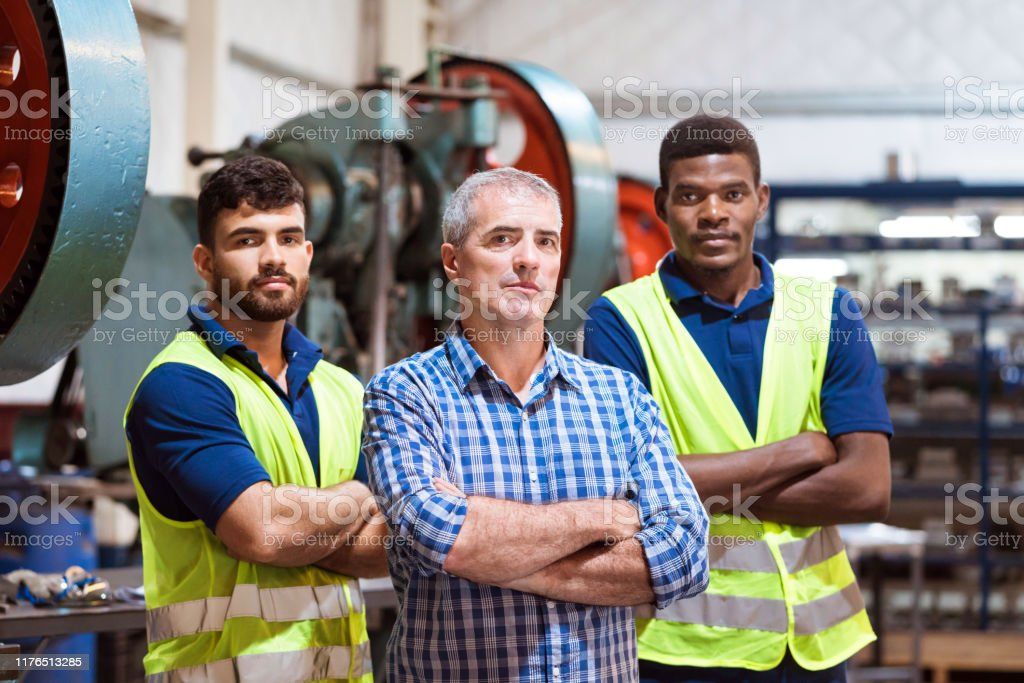 Portrait of confident male workers in factory Portrait of confident male workers standing in factory. Colleagues are with arms crossed working in manufacturing company. Young engineers are wearing reflective clothing. 20-24 Years Stock Photo