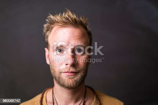 Portrait of confident mid adult man. Close-up of handsome male is having blond hair. He is against blackboard.