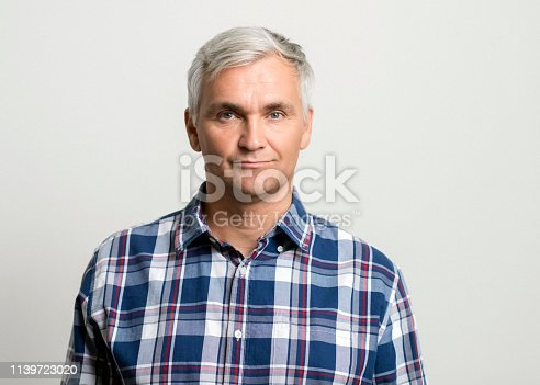 Portrait of confident mature man. Close-up of handsome male is on gray background. He is wearing plaid blue shirt.