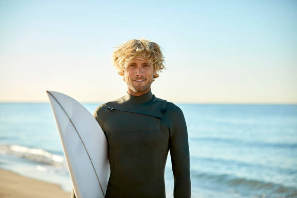 Portrait of confident man with surfboard at beach Portrait of confident mid adult man carrying surfboard at beach. Smiling male surfer is wearing wetsuit against sea. He is on summer vacation. wetsuit stock pictures, royalty-free photos & images