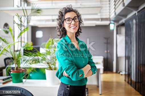 Portrait of happy mature businesswoman standing with her arms crossed. Mid adult female looking at camera and smiling while standing in office.