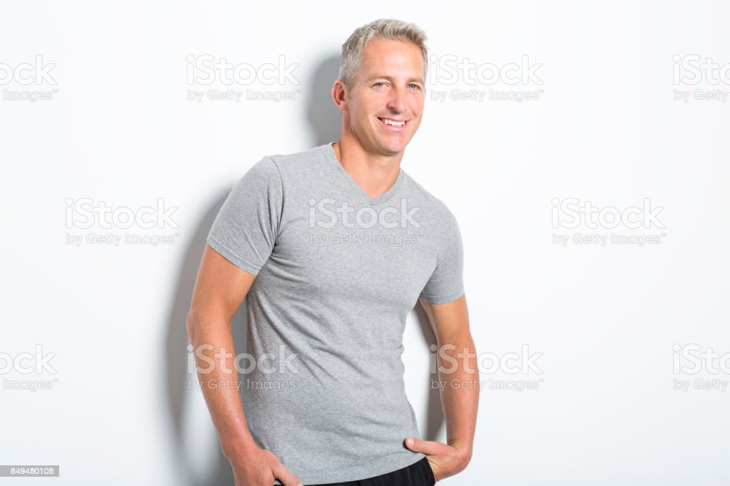 a07e60a9b Portrait of confident mature man standing on white background - Stock image  .