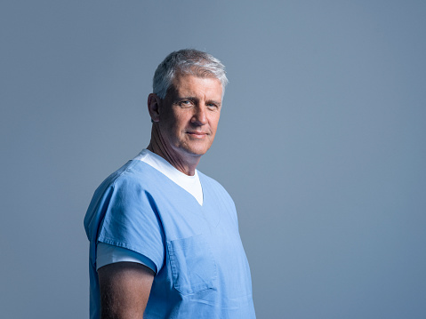 Portrait of male doctor in scrubs. Mature medical professional is against gray background. He is confident.