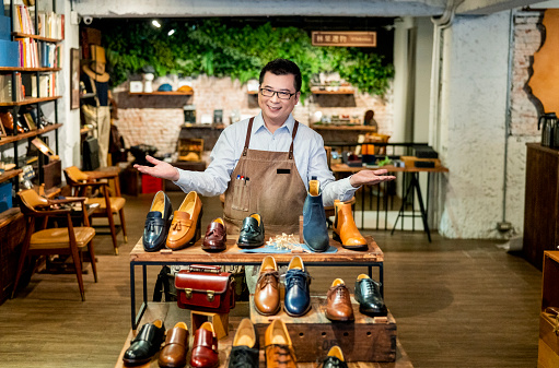 istock Portrait of confident owner gesturing by shoe rack 1158120074