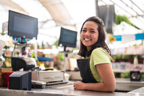 portrait of confident owner leaning on checkout counter at flower shop - store counter stock photos and pictures