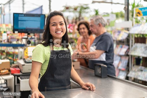 istock Portrait of confident owner leaning on checkout counter at flower shop 1037572242
