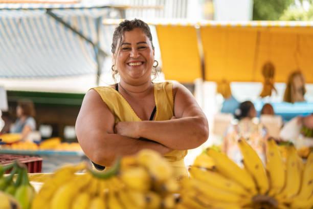 ritratto di proprietario fiducioso - vendere banane al mercato degli agricoltori - bancarella foto e immagini stock