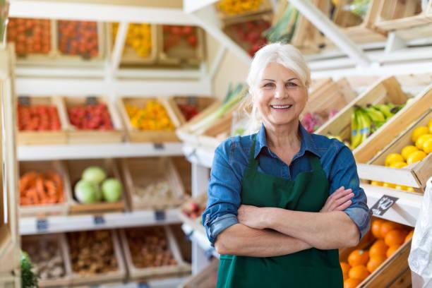 portret van vertrouwen eigenaar met arms gekruiste staande in kleine supermarkt - groenteboer stockfoto's en -beelden