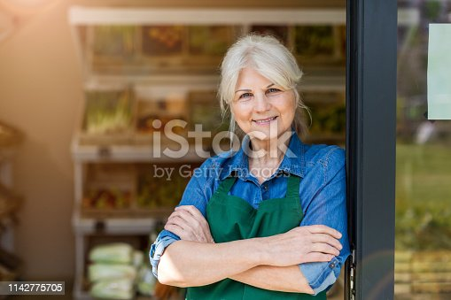 istock Portrait of confident owner with arms crossed standing in small grocery store 1142775705
