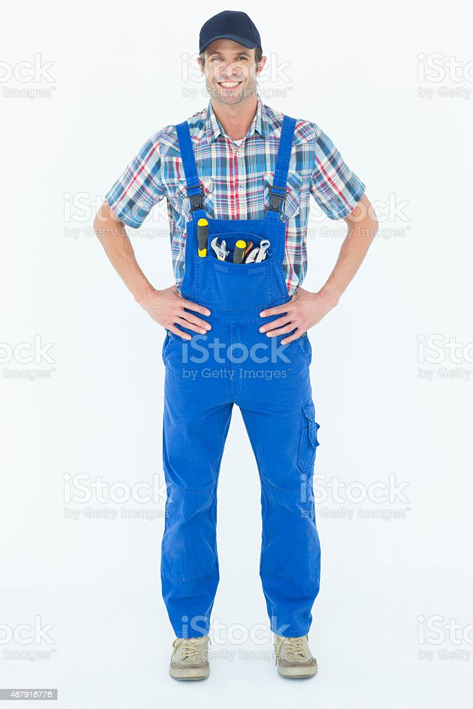 Portrait of confident plumber with hands on hip stock photo