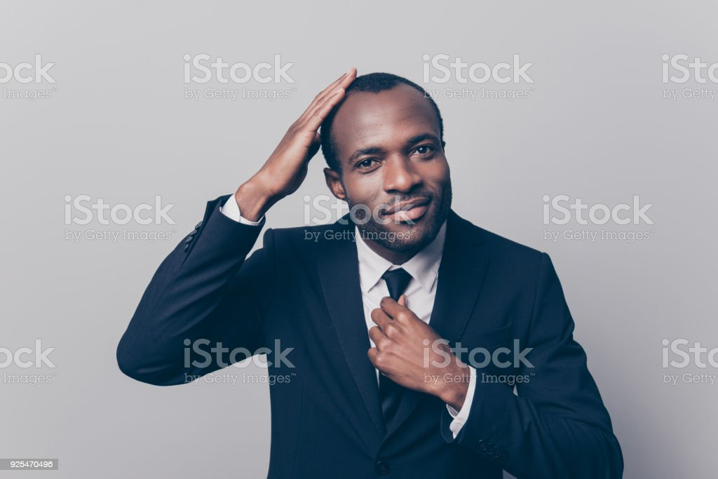 Portrait of confident satisfied cheerful calm peaceful handsome attractive afro man wearing formal outfit touching his hair and correcting tie isolated on gray background stock photo