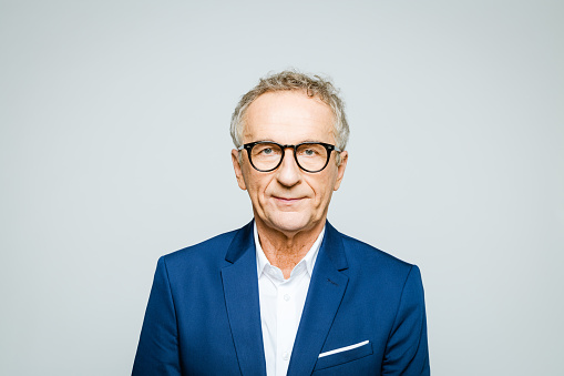 Portrait of elderly man wearing elegant suit and eyeglasses looking at camera. Senior entrepreneur, studio shot against grey background.