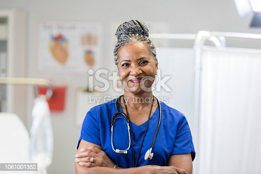 In this portrait, an African American senior female doctor smiles for the camera in an exam room with her arms folded.  She is wearing scrubs and a stethoscope.