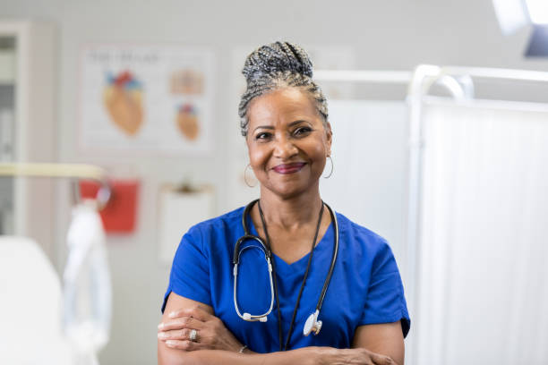 Portrait of confident senior female doctor in scrubs In this portrait, an African American senior female doctor smiles for the camera in an exam room with her arms folded.  She is wearing scrubs and a stethoscope. nurses stock pictures, royalty-free photos & images