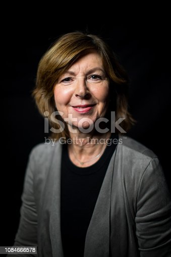 Portrait of confident senior woman wearing casuals on black background. Happy senior female looking at camera.
