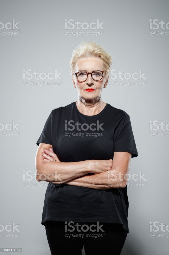Portrait of confident senior woman Powerful senior woman wearing black clothes, standing with arms crossed against grey background, staring at camera. Studio shot. Active Seniors Stock Photo