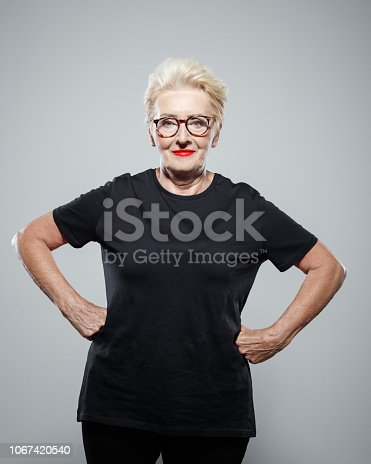 Powerful senior woman wearing black clothes, standing with hands on hips against grey background, smiling at camera. Studio shot.