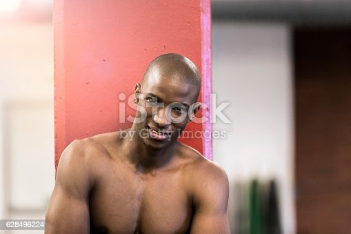 1069872470istockphoto Portrait of confident shirtless athlete in gym 628496224