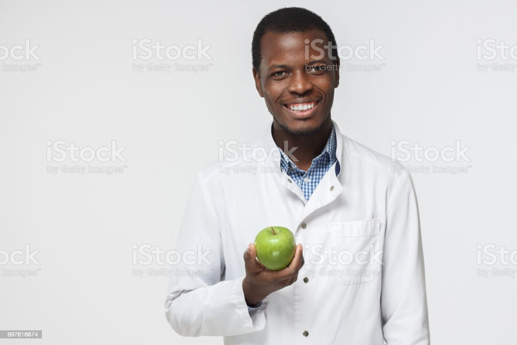 Portrait of confident smiling young african dentist, holding green apple on gray background stock photo