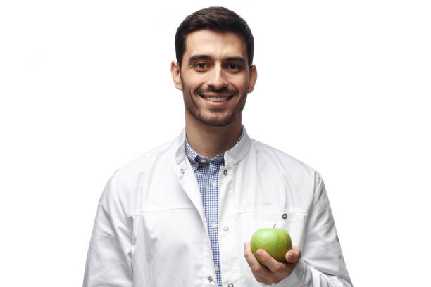 Portrait of confident smiling young man dentist, holding green apple on white background Portrait of confident smiling young man dentist, holding green apple on white background male likeness stock pictures, royalty-free photos & images
