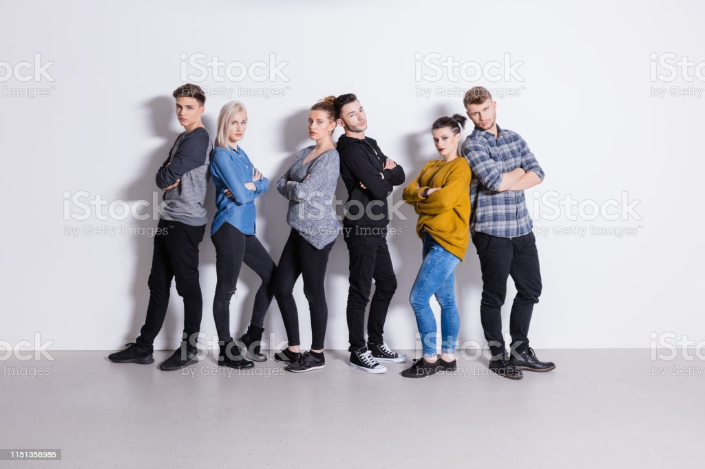 Portrait of confident students back to back Portrait of confident students standing back to back. Fashionable men and women are wearing casuals. They are against white background. 18-19 Years Stock Photo