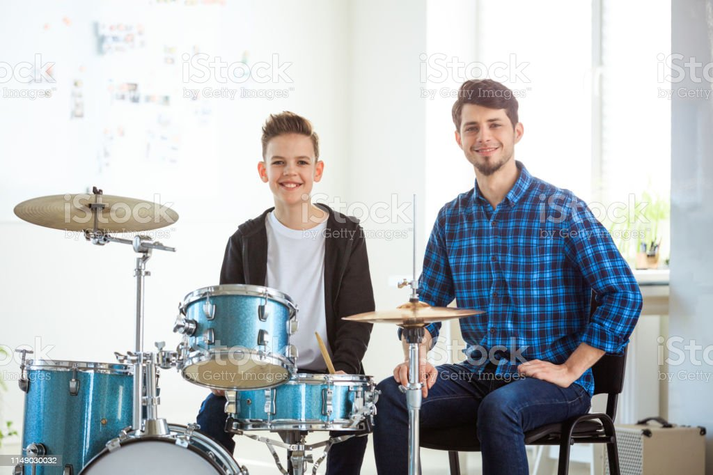 Portrait of confident trainer and student at class Portrait of smiling trainer with student in music class. Confident instructor teaching to play drums in conservatory. They are in casuals. 12-13 Years Stock Photo